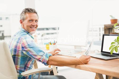 Smiling casual designer editing photos with computer