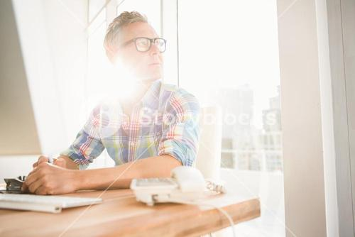 Casual designer sitting and daydreaming at his desk