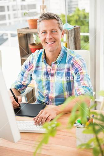 Smiling casual designer using computer and digitizer