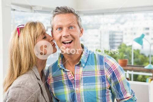 Casual designer giving her colleague kiss on cheek