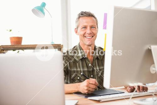 Smiling casual designer working with digitizer