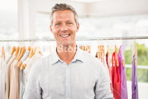 Smiling man in front of clothing rail