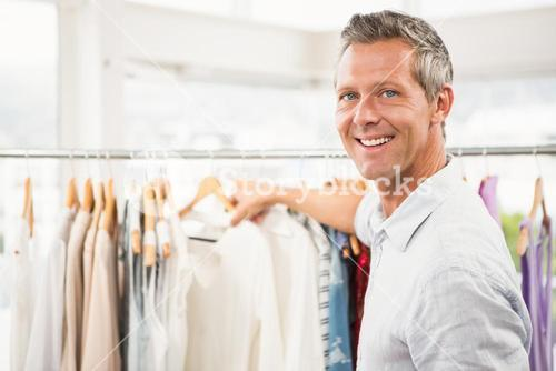 Smiling man browsing clothes