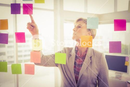 Casual businesswoman reading sticky notes