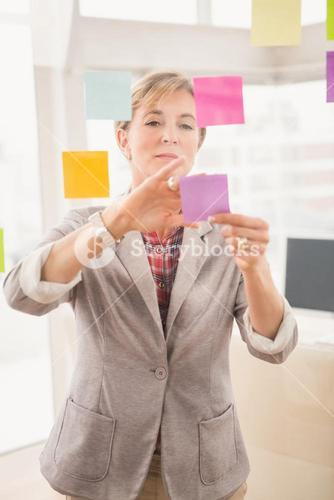 Casual businesswoman putting sticky notes on glass