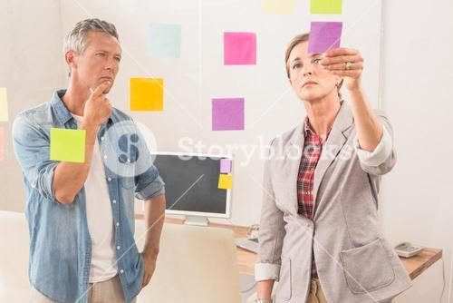 Casual business colleagues reading sticky notes