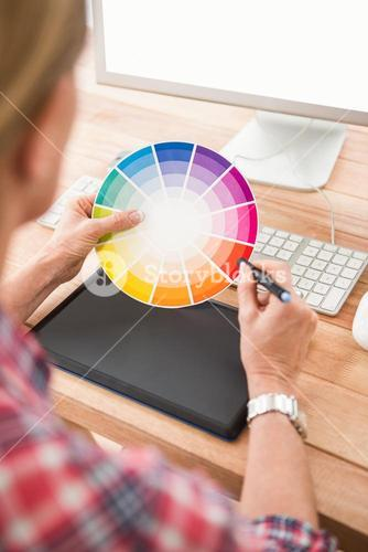 Casual designer working with digitizer and colour chart