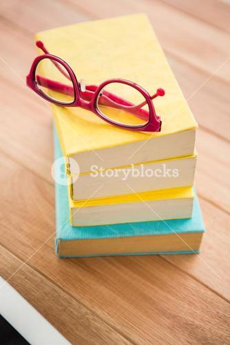 Red reading glasses on stack of books