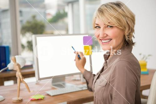 Smiling casual designer pointing blank computer screen