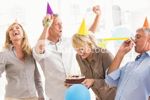 Casual business people celebrating birthday and having fun