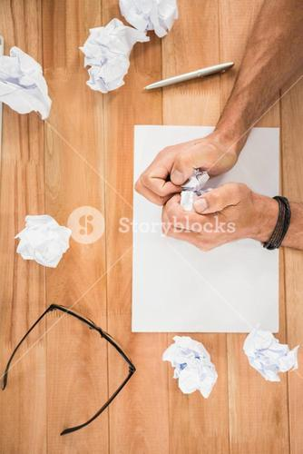 Hands crumpling paper on wooden desk
