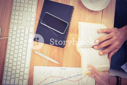 Businessman reading book on wooden desk