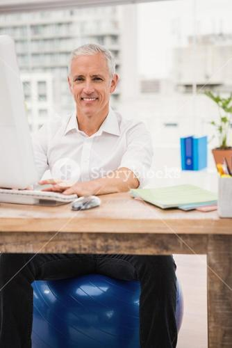 Smiling casual businessman sitting on exercise ball at desk