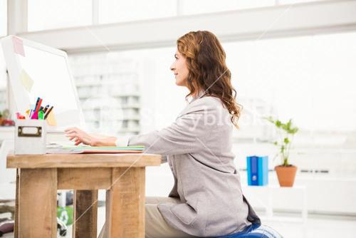 Casual businesswoman sitting on exercise ball while working