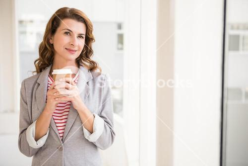 Smiling casual businesswoman holding take-away cup