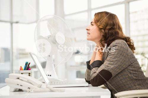 Casual businesswoman being cooled by ventilator