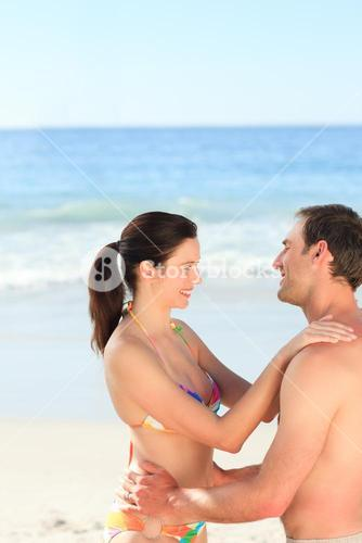 Adorable couple hugging on the beach