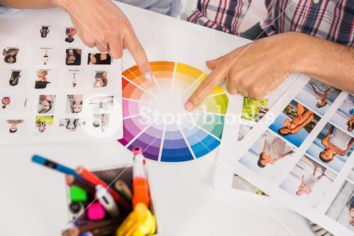 Casual designers working with colour chart and photographs