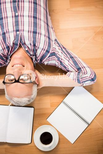 Smiling man lying on floor surrounded by office items