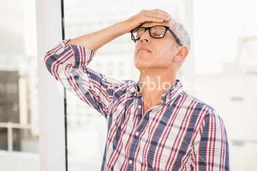 Troubled casual businessman leaning against window
