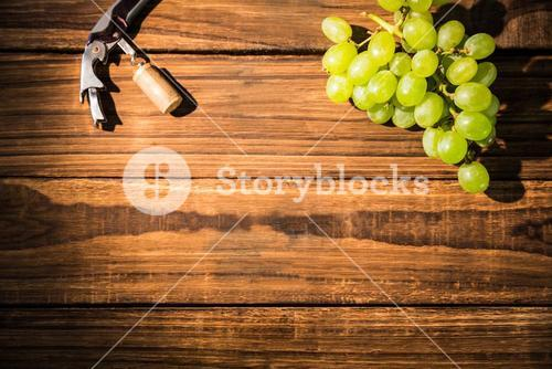 Grapes and corkscrew on table