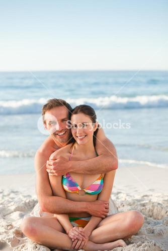 Enamored couple hugging on the beach