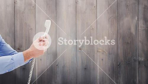 Composite image of businessman holding phone