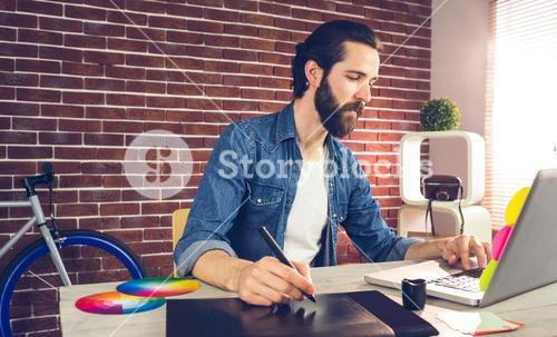 Businessman writing on graphic tablet while using laptop