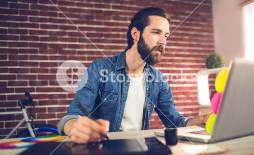 Creative businessman writing on graphic tablet while using laptop