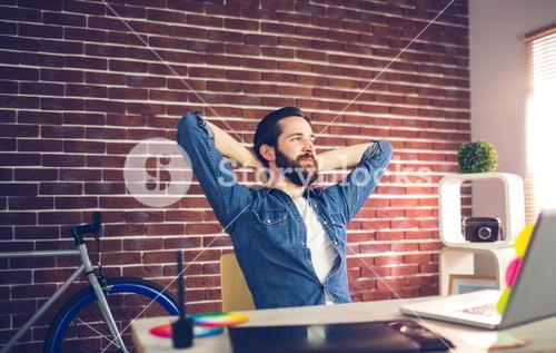 Thoughtful businessman relaxing in creative office