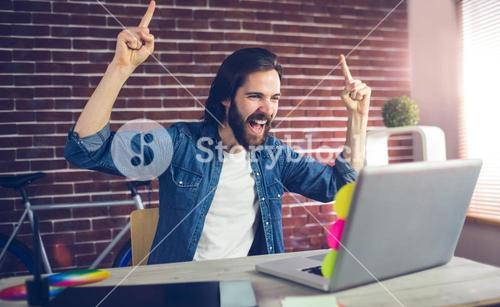 Happy creative businessman with arms raised looking at laptop