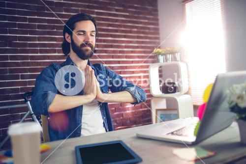 Businessman with hand clasped doing yoga