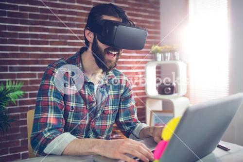 Happy creative businessman wearing 3D video glasses at office