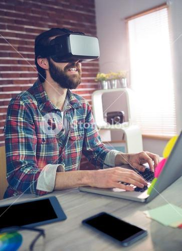 Creative businessman using 3D video glasses and laptop
