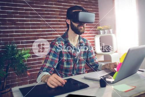 Serious creative businessman using 3D video glasses and laptop