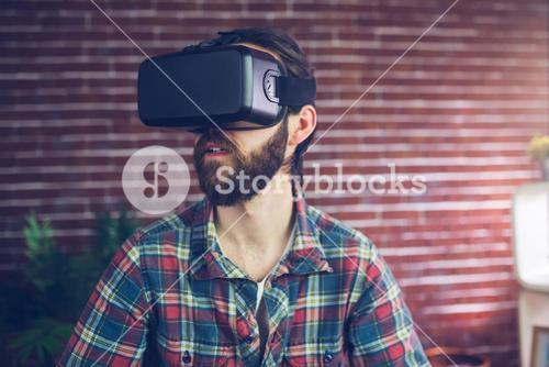 Creative businessman wearing 3D video glasses while looking away
