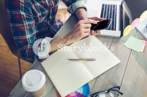 Midsection of creative editor using cellphone