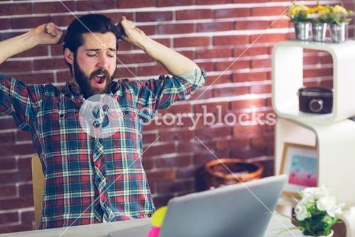 Creative businessman yawning with hands raised