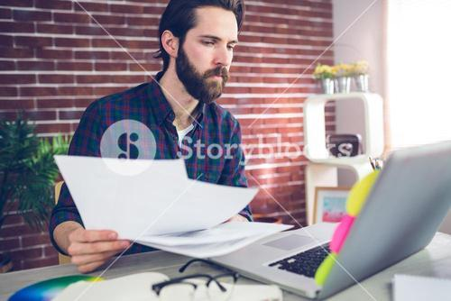 Creative businessman with documents using laptop