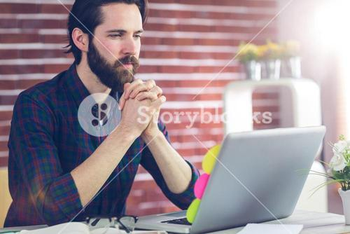 Focused editor with hand clasped using laptop