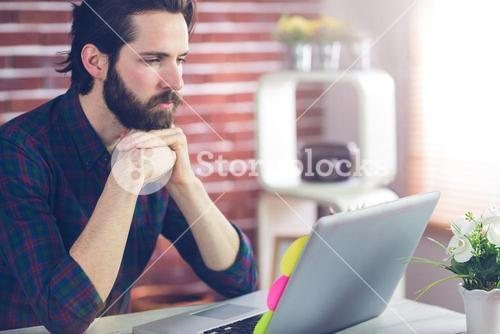Serious editor with hand clasped using laptop