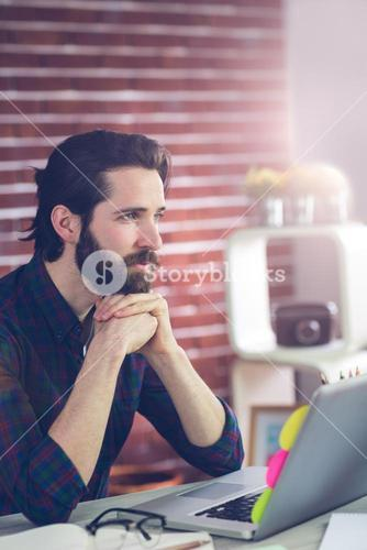 Thoughtful editor with hand clasped using laptop