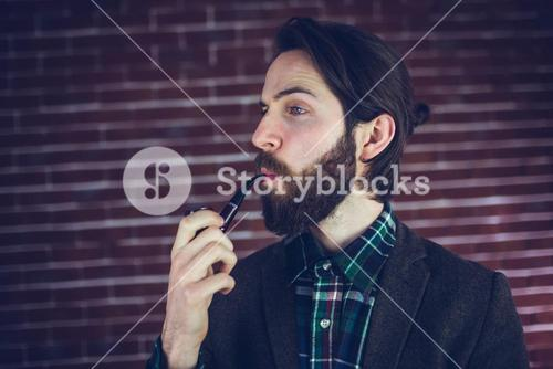 Fashionable man smoking pipe