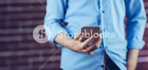 Midsection of man holding cellphone