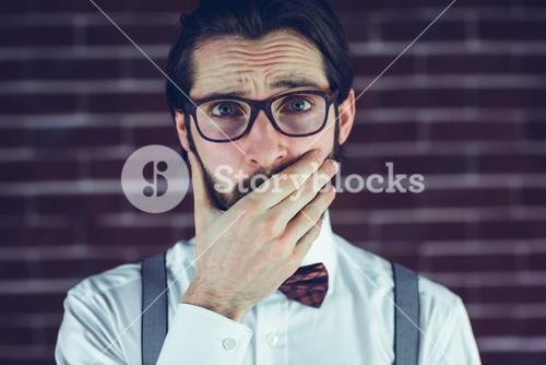 Portrait of nervous man covering mouth