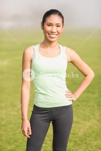 Smiling sporty woman with hand on hip