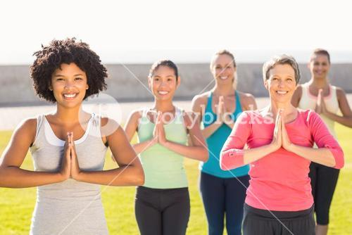 Smiling sporty women doing prayer position in yoga class