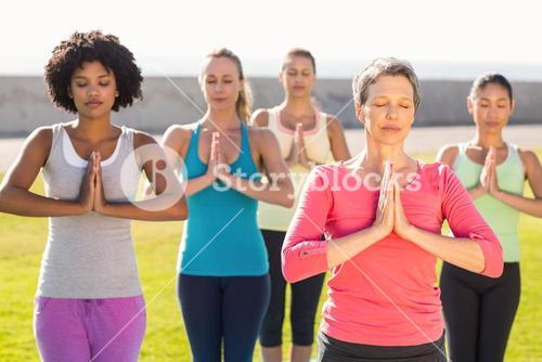 Peaceful sporty women doing prayer position in yoga class