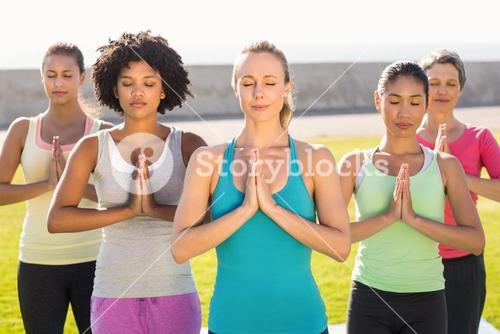 Peaceful sporty women doing prayer position