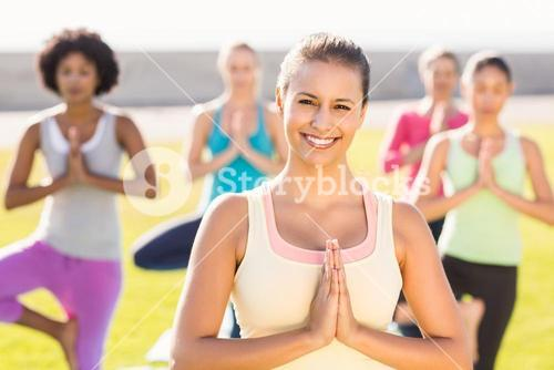 Smiling sporty brunette doing yoga in yoga class
